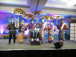 "The 2019 cast of the ""Shoko Shiranami Gonin Otoko"" performance. Kneeling in front is the Kojyo, played by Chef Alan Wong. Standing from left are: Meakashi Kingoro (Kevin Ching), and dorobo Nango Rikimaru (Kristin Alm Kamakahi), Akaboshi Jyuzaburo (Daisuke ""Duke"" Ueda), Tadanobu Rihei (Ray Tsuchiyama), Benten Kozo Kikunosuke (Jennifer Okubo) and Nippon Daemon (Ala Kinuhata)."