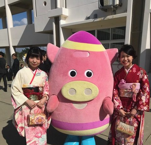 Mizuki and her friend pose for a photo with Yomitan's official mascot, Yomiton.