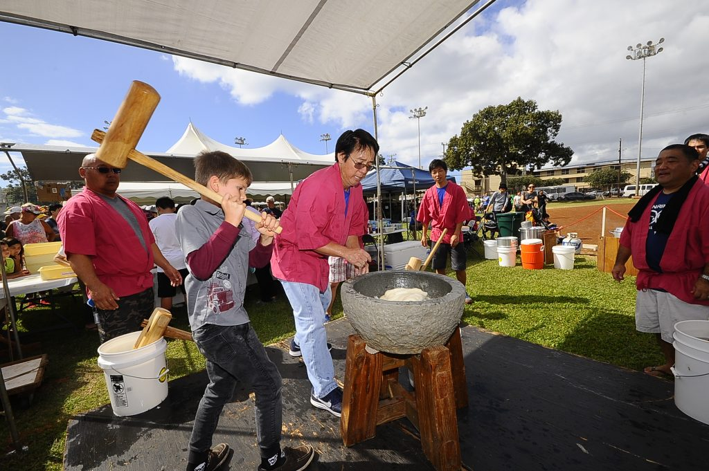 A young boy tries his hand at pounding mochi the traditional way.