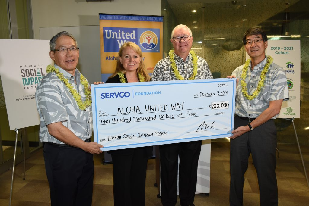 Servco Foundation presents a check for $200,000 to Aloha United Way to launch the Hawaii Social Impact Project. From left: Rick Ching, Servco president/COO; Elizabeth McFarlane, AUW vice president for community impact; Norm Baker, AUW COO; and Mark Fukunaga, Servco chairman and CEO. (Photo courtesy Servco Pacific Inc.)
