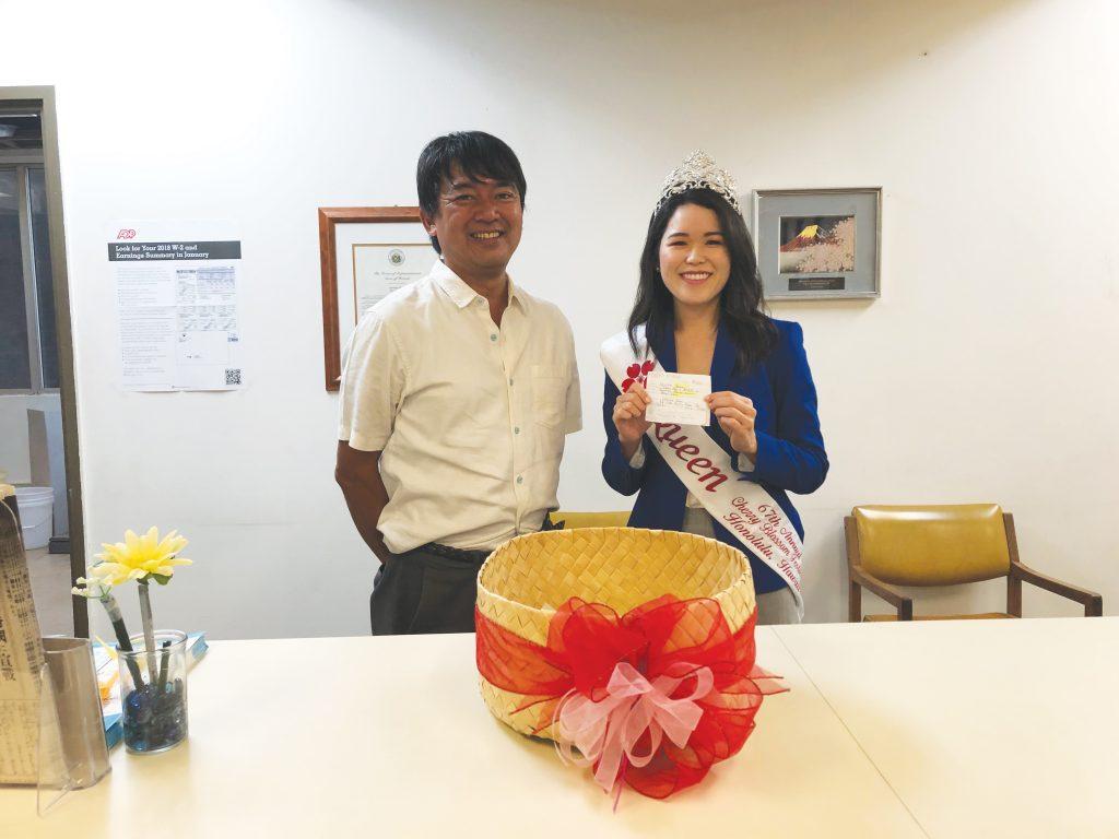 "Cherry Blossom Festival queen Lauren Sugai randomly drew the winning ballots of the 36th ""Guess the Cherry Blossom Festival Queen"" contest. She is pictured with Hawaii Hochi, Ltd. president Taro Yoshida."