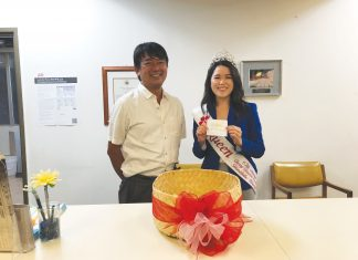 "Cherry Blossom Festival queen Lauren Sugai randomly drew the winning ballots of the 36th ""Guess the Cherry Blossom Festival Queen"" contest. She is pictured with Hawaii Hochi, Ltd. president Taro Yoshida."
