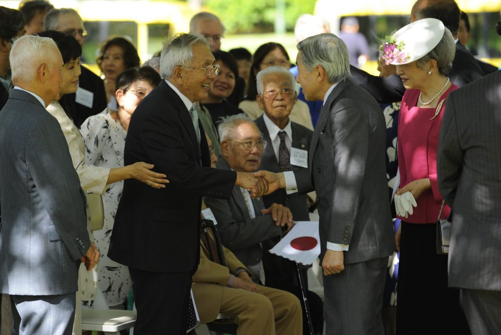 Emperor Akihito and then-Hawaii Hochi president and publisher Paul Yempuku exchange a handshake at Kapi'olani Park, where the imperial couple met with community leaders. Yempuku promised the emperor that he would continue publishing the Hawaii Hochi Japanese-language newspaper at least until its 100th anniversary in 2012. (Hawaii Hochi photo)