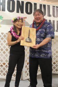 "Sandra Ishihara-Shibata was recognized as the Honolulu Hiroshima Kenjin Kai's 2018 outstanding member. HHKK president Wayne Miyao presents her with the ""trophy"" given to all of the kenjinkai's outstanding members — an official okonomiyaki spatula."