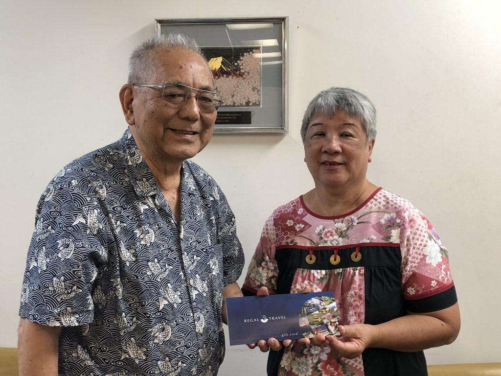 Regal Travel co-owner and CEO Ray Miyashiro presents his company's $500 first prize travel voucher to winner Jemalee Wong of Käne'ohe. Wong works as her mother's caregiver.