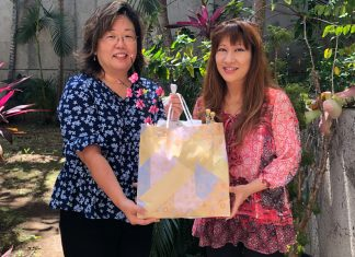 Shirley Iida (left) presents third prize winner Laurie Ide of Pearl City with an Iida's gift basket filled with precious Japanese goods.