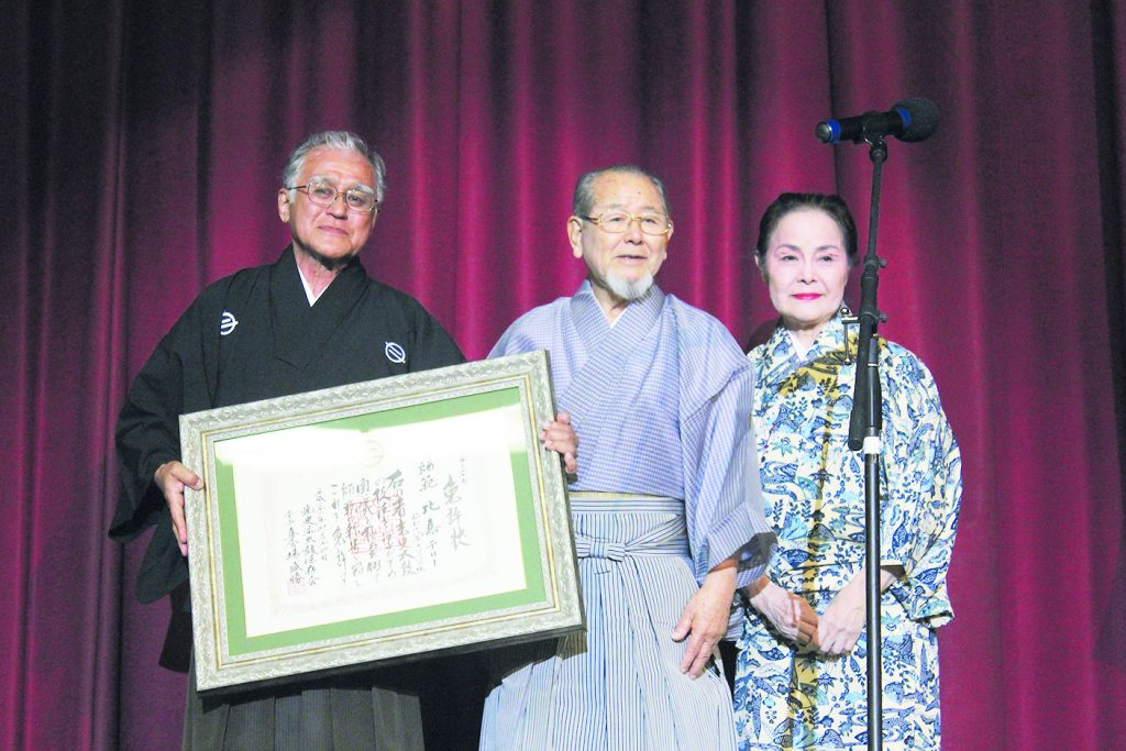 Terry Higa-Sensei holds his shihan (master teacher) certificate after Morikatsu Kishaba-Sensei (center) presented it to him during the performance. Pictured with them is Kimiko Shimabukuro-Sensei from Okinawa, who was Hawaii Taiko Kai's first teacher when the group organized in 1987.