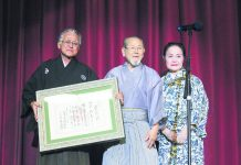 Terry Higa-Sensei holds his shihan (master teacher) certificate after Morikatsu Kishaba-Sensei (center) presented it to him during the performance. Pictured with them is Kimiko Shimabukuro-Sensei from Okinawa, who was Hawaii Taiko Kai's first teacher when the group organized in 1987.