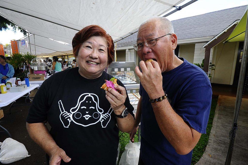Two volunteers take a break to enjoy a hotdog with daikon relish. (Photos by Wayne Shinbara)