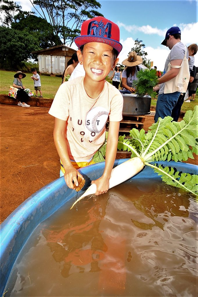A young boy scrubs his daikon clean before taking it home to share with his family.