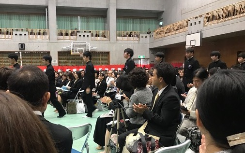 The Yomitan High School graduates enter the school gymnasium to begin the graduation ceremony with family and friends in attendance.