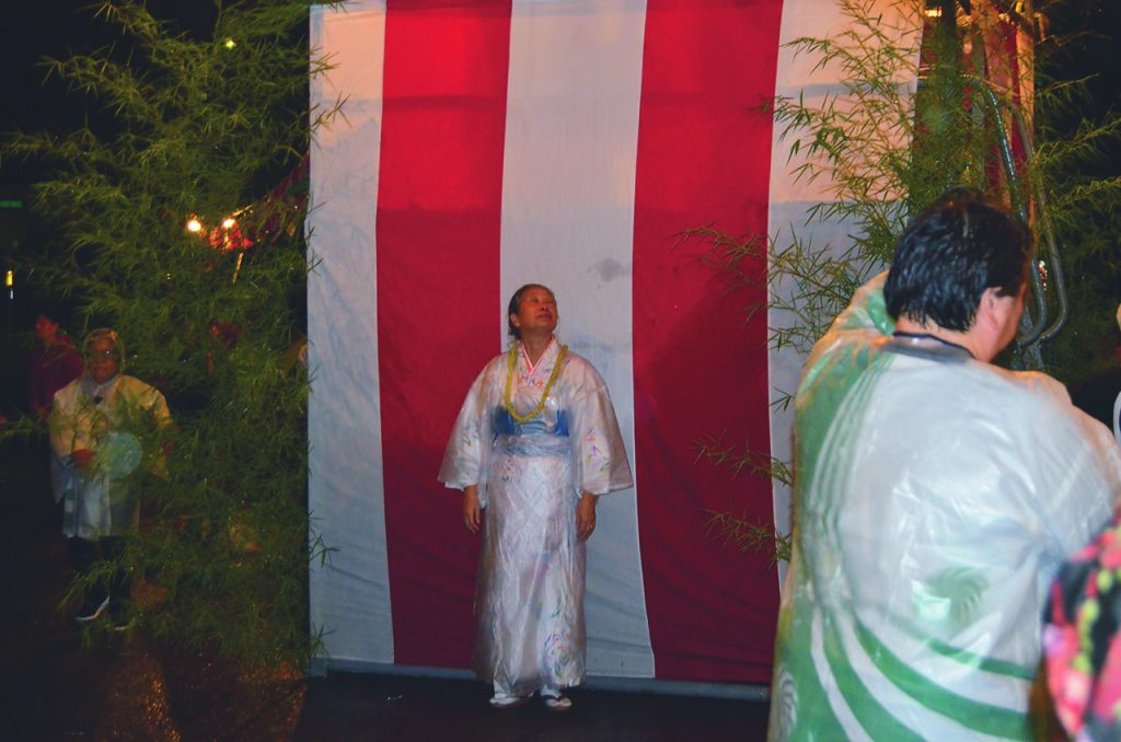 At Honomu Henjoji, the first temple bon dance of the season, Jane Heit looks up at the skies with hopeful eyes.