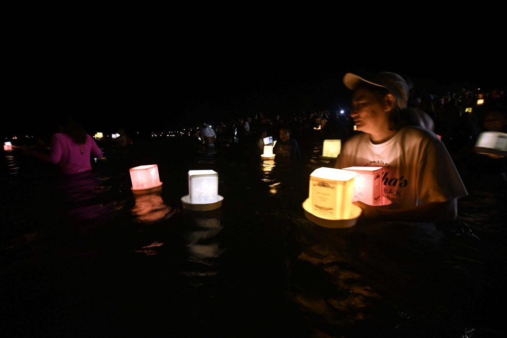 Several people entered the ocean to place their lanterns in the water.
