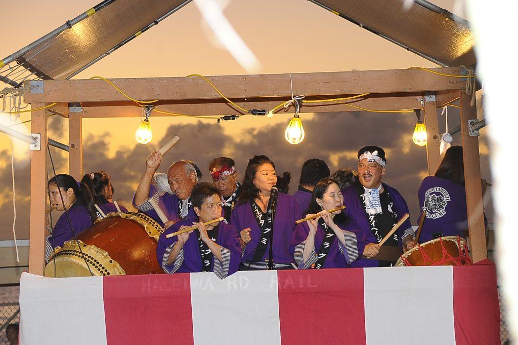 Enthusiastic Aiea Taiheiji Yagura Gumi musicians perform bon dance music in the yagura at sunset.