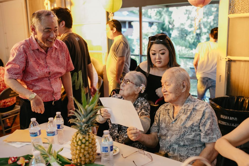 """Cousin Richard """"Dickie"""" Shimabukuro (standing, left), who flew in from his home in Utah, catches up with his Aunty Sueno (sister of his late mother Matsue Nakasone Shimabukuro) and Uncle Thomas Murakami and their granddaughter, Sheri Morishige. It was the first Nakasone family reunion that Dickie attended. He told writer (and his cousin) Dan Nakasone that hearing the Okinawan music for the first time in decades brought tears to his eyes. (Michelle Nakasone Photography)"""