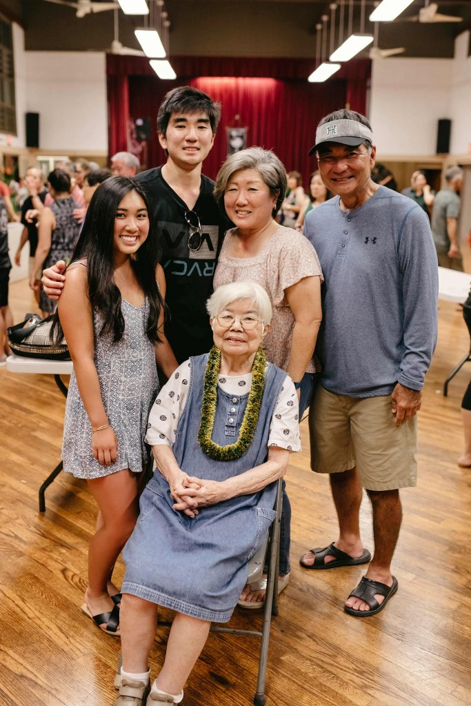 Uncle Jimmy Iha encouraged the Sansei cousins to keep the Nakasone 'ohana together by holding reunions. Uncle Jimmy passed in 2011, but his spirit has been with the family at every reunion. Pictured here are some of his family members: wife Marian (seated), grandchildren Kadee and Derren, and daughter-in-law Karen and son Derek. (Michelle Nakasone Photography)