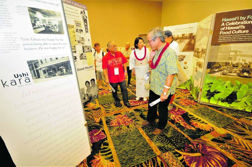 Consul General of Japan Koichi Ito reads the Okinawan Restaurants display panels while his wife Misako and their festival escort, HUOA past president Vince Watabu, talk with former Columbia Inn owner Gene Kaneshiro (obscured) about the project. (Photo by Wayne Shinbara)