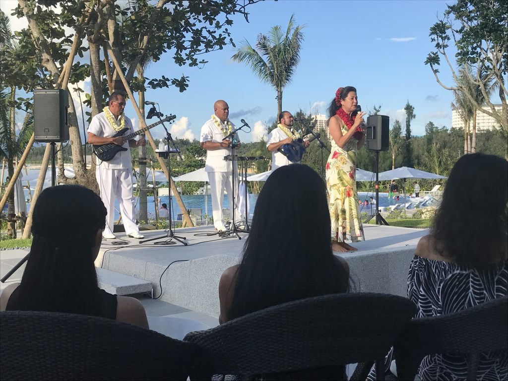 Halekulani's hula dancer Kanoe Miller addresses the opening day audience at the Halekulani Okinawa. Behind her are musicians (from left) Danny Naipo on bass, Ocean Kaowili on steel guitar and Eric Lee on guitar.