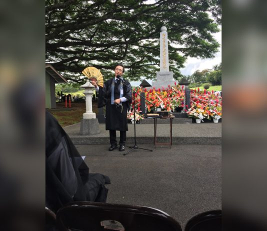 The Rev. Satoshi Tomioka of Puna Hongwanji delivers the sermon at a past Ireisai service held at 'Alae Cemetery, located just north of Hilo town. Local Japanese community groups and temples offer floral arrangements at the Ireito monument. (Photo by Eloise Hiura)