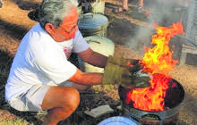Man with gloves around fire for 'Hands on Raku'