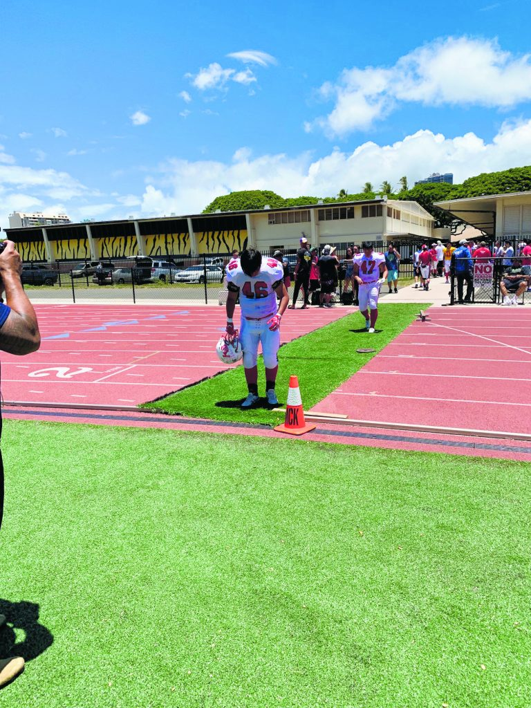Kosei Gakuen players bow as they step onto the football field.
