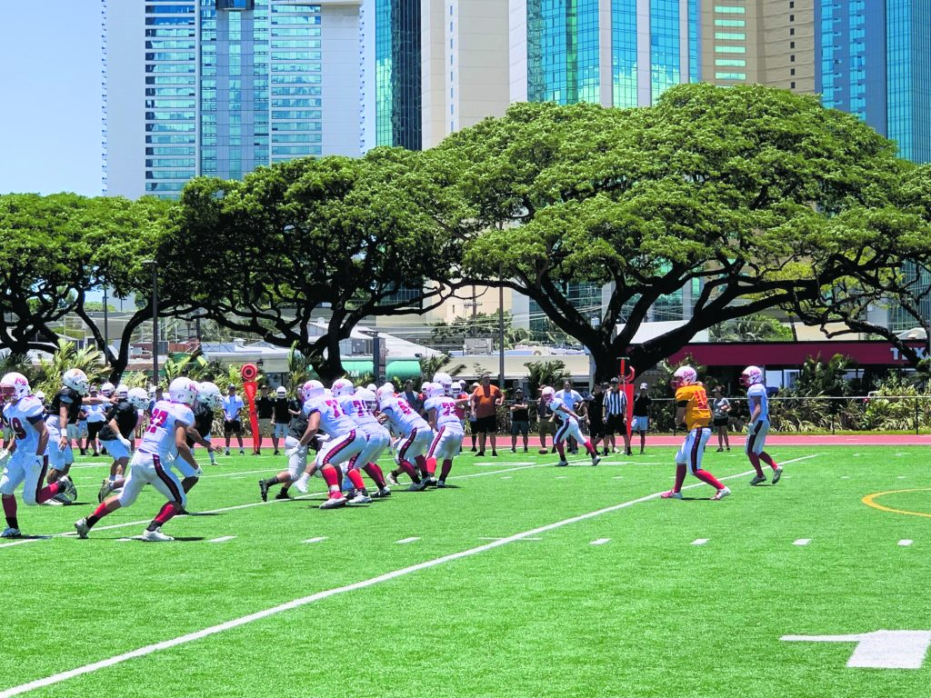 The Lotus players scrimmaging against Pac-Five's Wolfpack football team at McKinley High School.