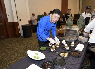 Chef Chai Chaowasaree plating his dish – shoyu and Kuba Awamori-braised pork belly in a steamed bun with cucumber namasu (Japanese pickles) and scallions. (Photo by Wayne Shinbara)