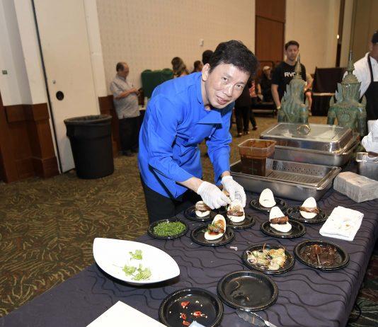 Chef Chai Chaowasaree plating his dish – shoyu and Kuba Awamori-braised pork belly in a steamed bun with cucumber namasu (Japanese pickles) and scallions. (Photo by Wayne Shinbara)