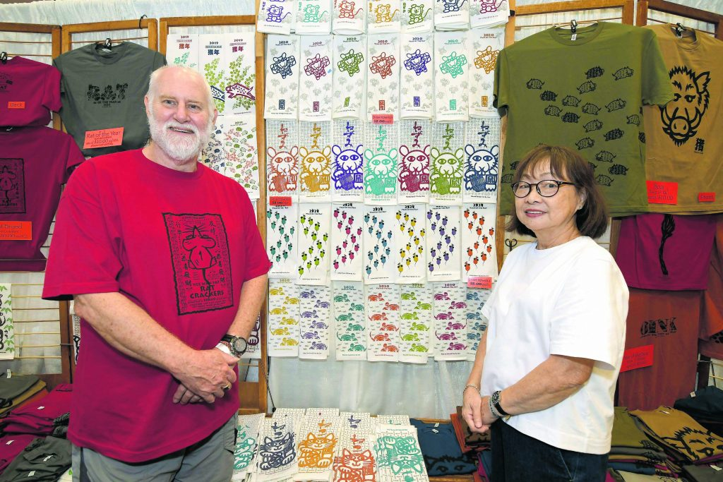 """Philip and Mieko Markwart of One by One Enterprises are familiar faces at craft fairs all over town. Philip and Mieko are both fiber and ceramic artists. Every year, they come up with creative and whimsical T-shirt and dishtowel designs centered on the coming year's zodiac animal. Notice Philip's """"Rat Crackers"""" T-shirt to celebrate 2020, the Year of the Rat."""