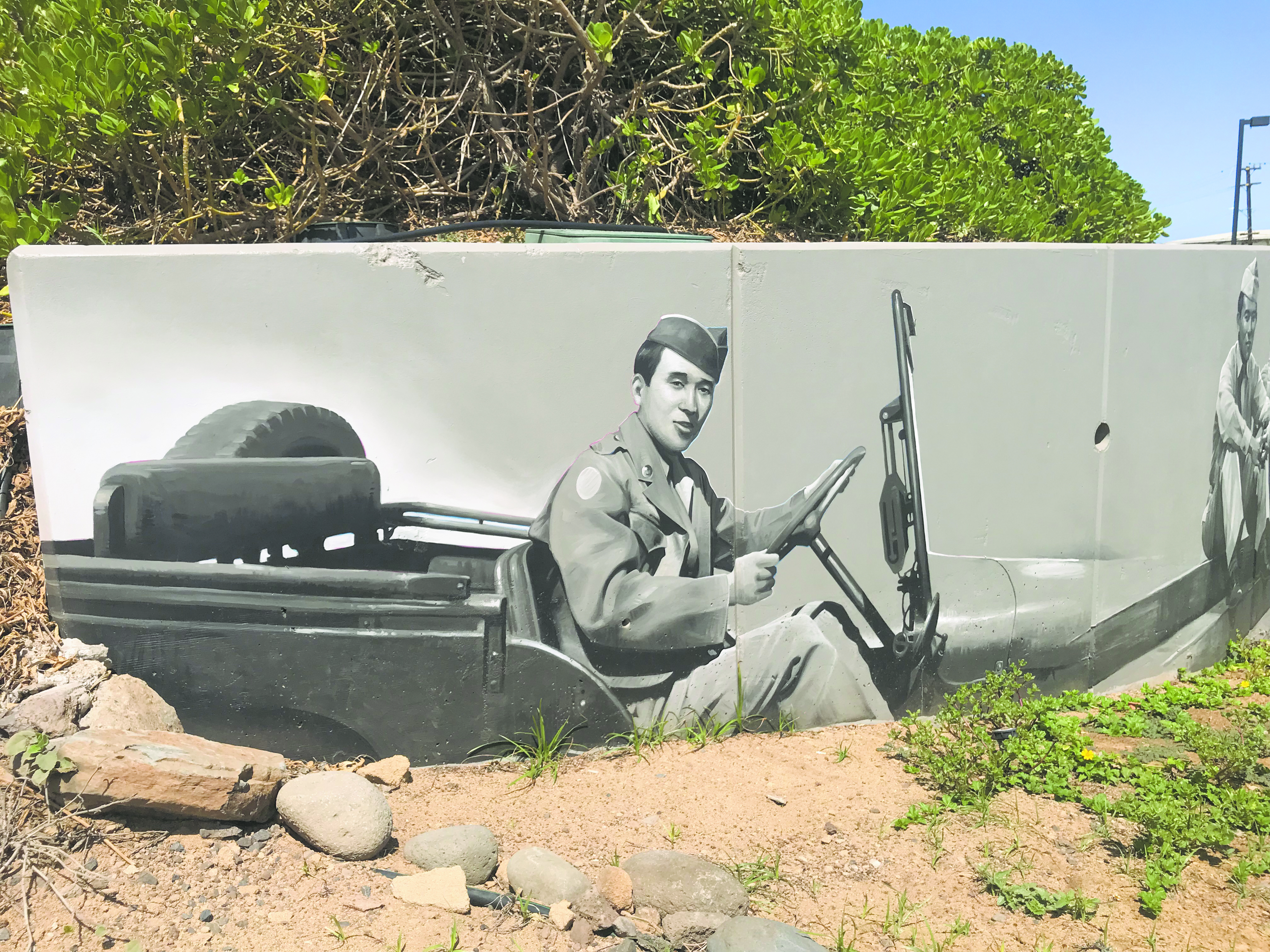 Maui artist Kirk Kurokawa chats with visitors recently at the Nisei Veterans Memorial Center, where he is painting a mural highlighting the World War II AJA soldiers.