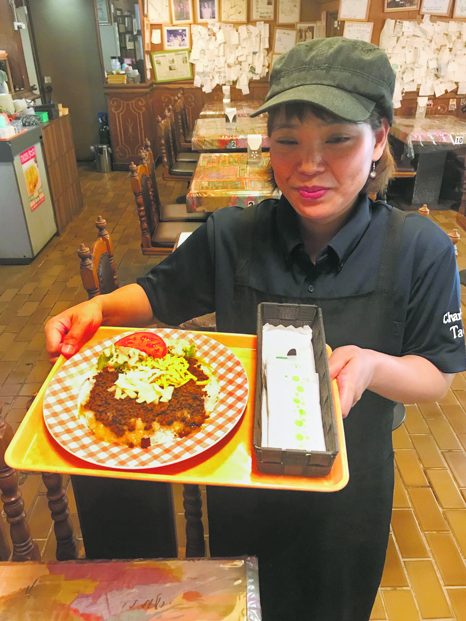 A server at Charlie's Tacos brings out Colin's taco rice order.