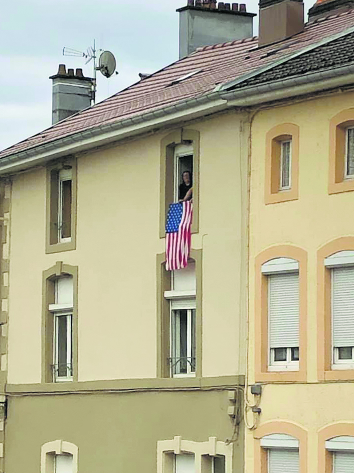 """An American flag hung from the window of an apartment in Bruyères. """"Gratitude to the citizens of Bruyères and the Vosges, and France, for understanding and embracing all this and for keeping their memories alive."""" — Congressman Ed Case"""