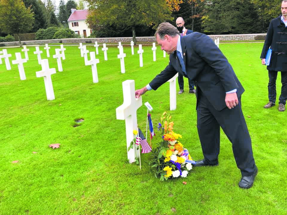 Congressman Ed Case places a House of Representatives challenge coin on the cross that stands over the grave of PFC Yoshio Tengwan of Lahaina, Maui, at the Épinal American Cemetery. Of the 5,255 Americans buried here, 13 served with the 100th/442nd, including two from Hawai'i.