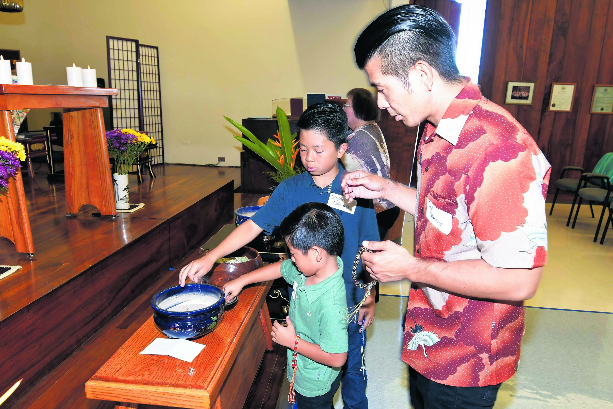 Brad Nakamura watches as his sons, Brayden and Camden, offer oshökö (incense) at the service. Brad's father, the Rev. Bruce Nakamura, previously served as resident minister of Jikoen Hongwanji.