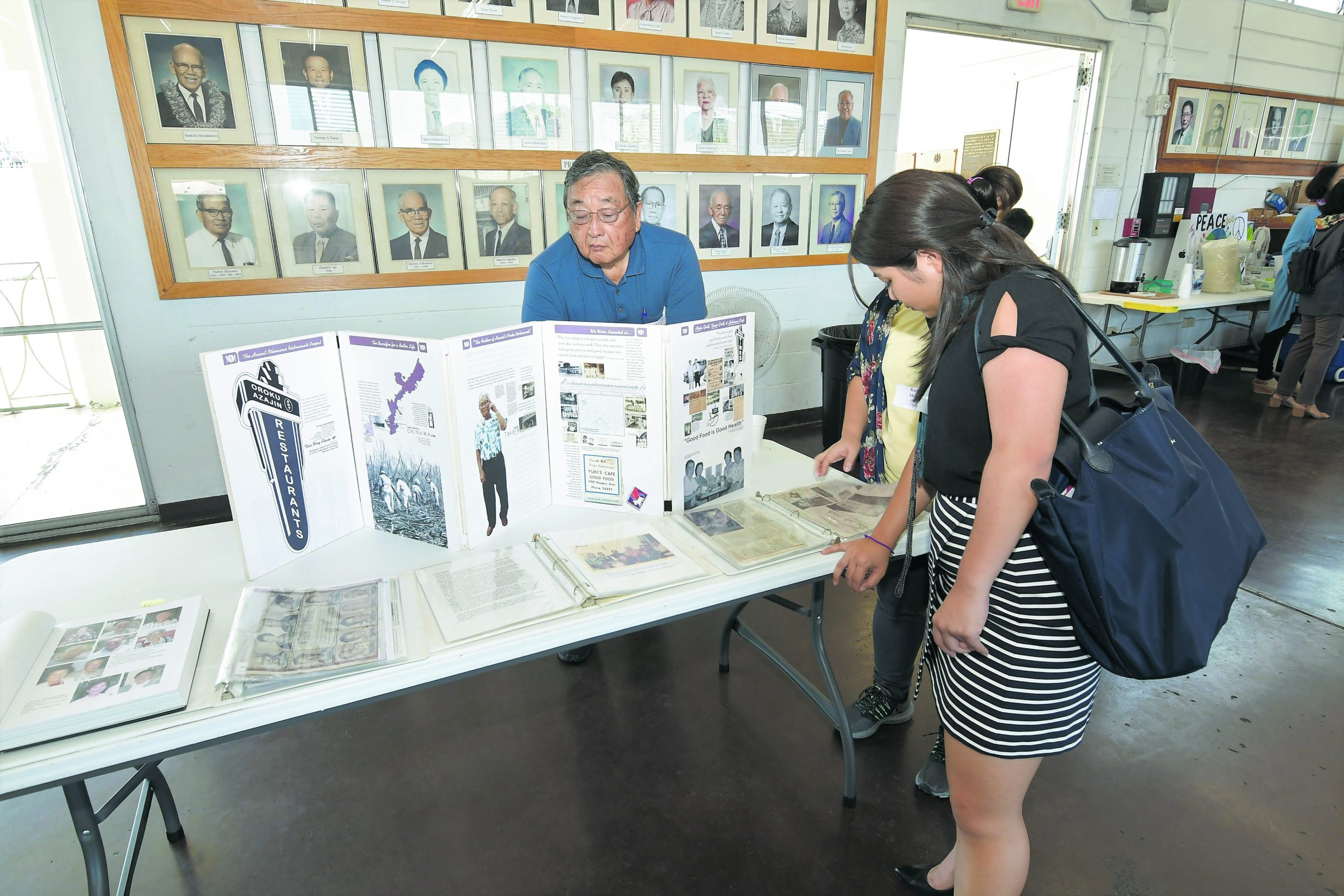 Wayne Toma and Marcie Moribe browse the Okinawan Restaurants Project tabletop display. Moribe's grandparents, the late Seizen and Fusae Hanashiro, both worked at — and retired from — KC Drive Inn. On the wall behind Toma are photographs of Jikoen's past presidents.