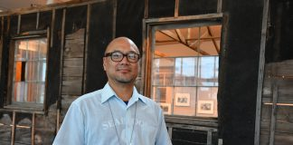 Clement Hanami, Vice President of exhibits and art director for the Japanese American National Museum in a reconstructed barracks building from the Heart Mountain Relocation Camp in Wyoming. The structure was reconstructed in the museum building.