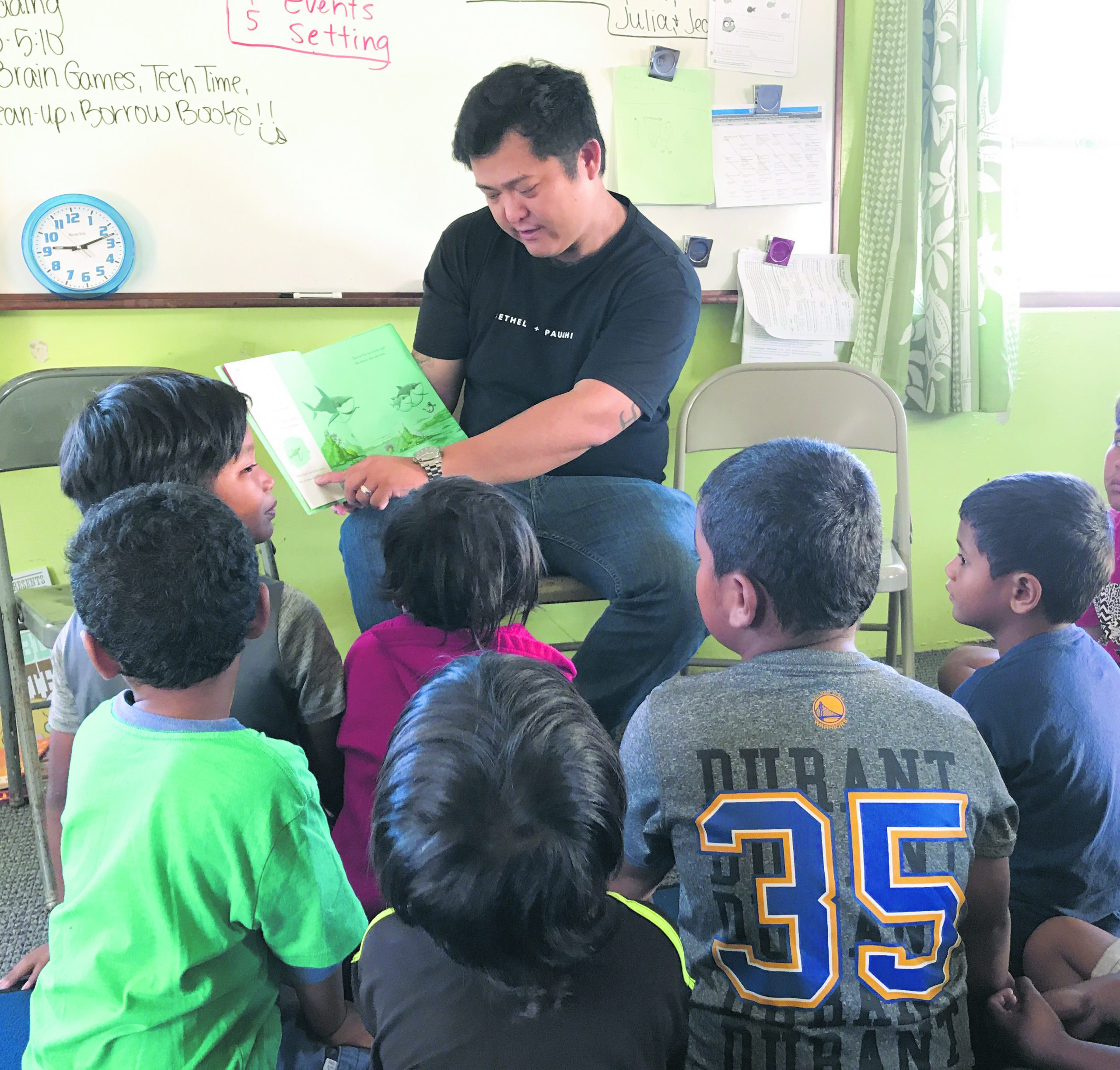 A HIHO volunteer reads to children.