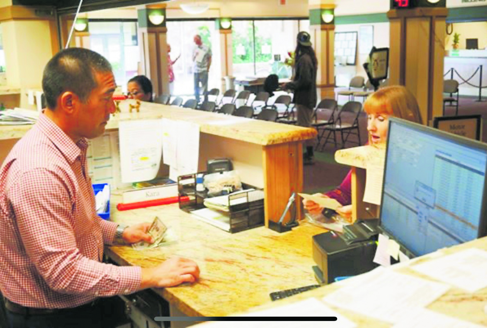 The hands-on mayor assists a Kaua'i resident at the Motor Vehicle Registration Office.