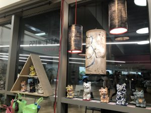 Wendy Kim Messier's lamps with shades and images of cats drawn on them hang above Suzanne Wolfe's porcelain Maneki Neko featuring a variety of glazed paintings.