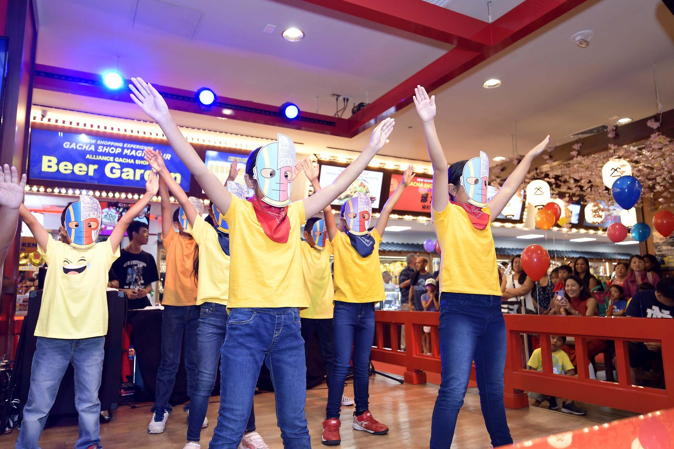 "The ""Kikaida Keiki Chorus"" from Hongwanji Mission School's after-school program, led by teacher Janice Terakawa, performed a medley of Japanese superhero songs with masks they made."