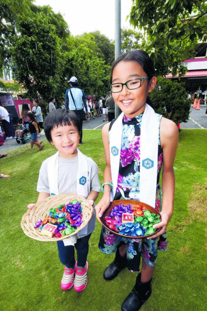 At Izumo Taishakyo Mission in Chinatown, 6-year-old Lena Amano and 10-year-old Aina Yamauchi offered sweet treats to shrine visitors after they had received their blessing.