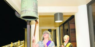 Bishop Shokai Kanai of Nichiren Mission in Nu'uanu observes as longtime member Sandra Taga rings the temple bell a few minutes before Jan. 1, 2020. The ringing of the bell signifies the arrival of the new year.
