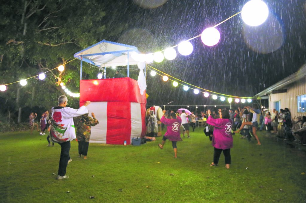 After a 10-year absence, Naalehu Hongwanji Mission on Hawai'i Island opened its doors to the public last Aug. 31 and observed obon with a bon dance. Members of Hongwanji's Hilo, Pahala, Kona and Kohala temples, along with Kona Jr. YBA members, helped the Naalehu Hongwanji members set up the grounds and also participated in the festival to welcome home the spirits of deceased loved ones . . . even in the pouring rain!