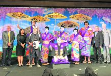"The 2020 cast and producers of the ""Shoko Shiranami Gonin Otoko"" performance. Kneeling in front is the Kojyo played by Neal Yokota. Standing behind the Kojyo, from left to right producers Ronald Ushijima and Rika Hirata, Meakashi Kingoro (Kurt Murao), Akaboshi Jyuzaburo (Ina Chang), Tadanobu Rihei (Kristine Wada), Benten Kozo Kikunosuke (Jill Kuramoto), Nippon Daemon (Brian Kealoha), and producers Robert Nagao and Gregg Mueller. Standing in back, Nango Rikimaru (Jacce Mikulanec)."