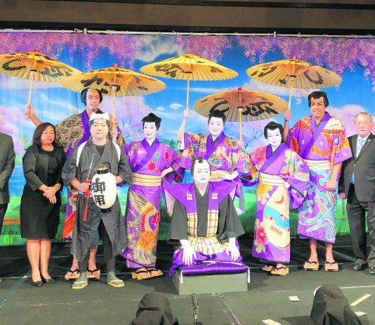"The 2020 cast and producers of the ""Shoko Shiranami Gonin Otoko"" performance. Kneeling in front is the Kojyo played by Neal Yokota. Standing behind the Kojyo, from left to right producers Ronald Ushijima and Rika Hirata, Meakashi Kingoro (Kurt Murao), Akaboshi Jyuzaburo (Ina Chang), Tadanobu Rihei (Kristine Wada), Benten Kozo Kikunosuke (Jill Kuramoto), Nippon Daemon (Brian Kealoha), and producers Robert Nagao and Gregg Mueller. Standing in back, Nango Rikimaru (Jacce Mikulanec)."