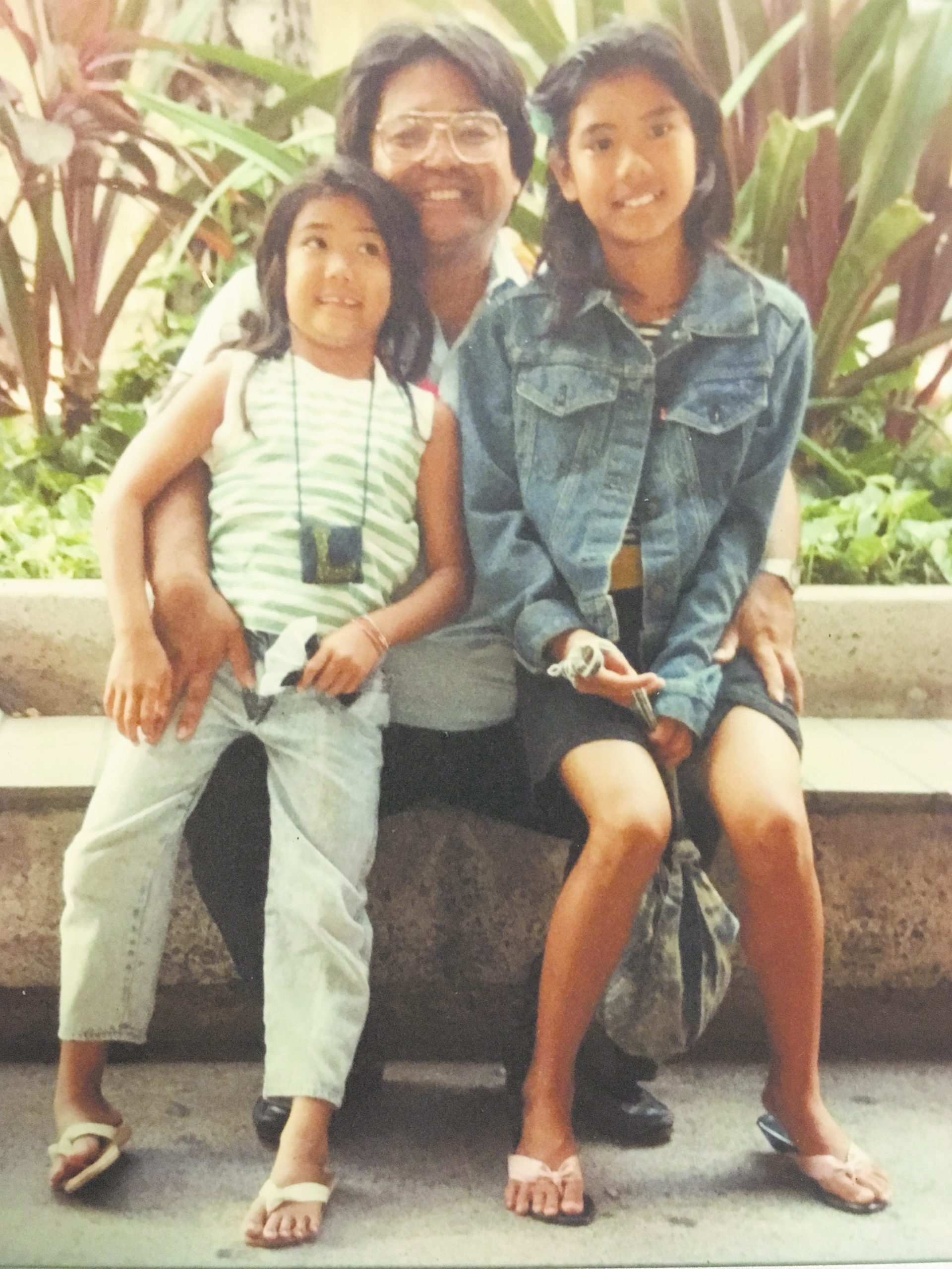 Lynn Miyahira (left) and her sister Ann are pictured with their dad, Wayne Miyahira, in 1989 at the Honolulu International Airport. At the time, Wayne was president-elect of the then-United Okinawan Association of Hawaii. He has just gotten off the plane after having traveled to Okinawa with 1989-90 president John Tasato and the UOA Study Tour. Lynn and Ann were at the airport to welcome their dad home. (Photo by Karleen Chinen)