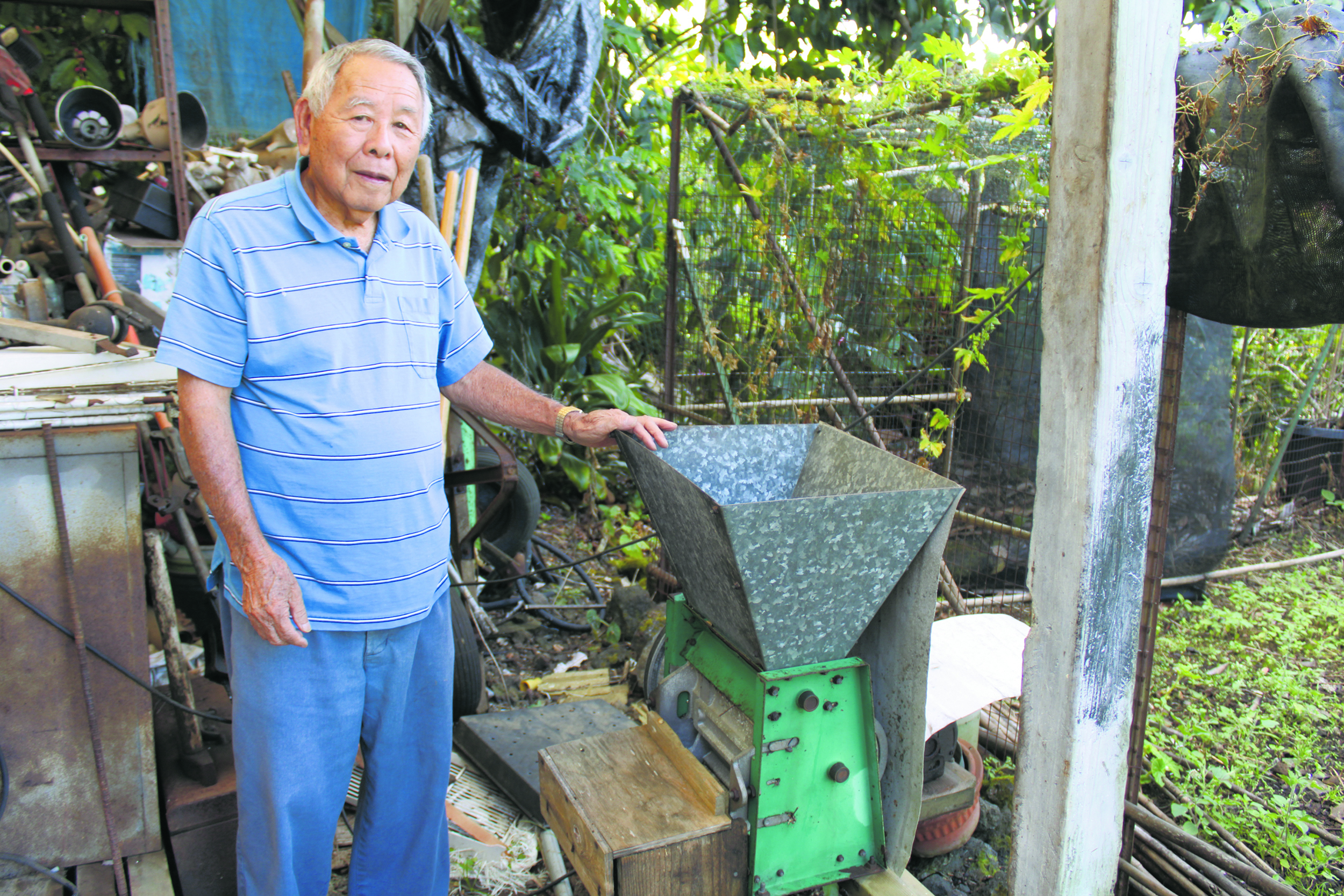 Takeo next to the machine that removes the skin and pulp from the coffee cherry.