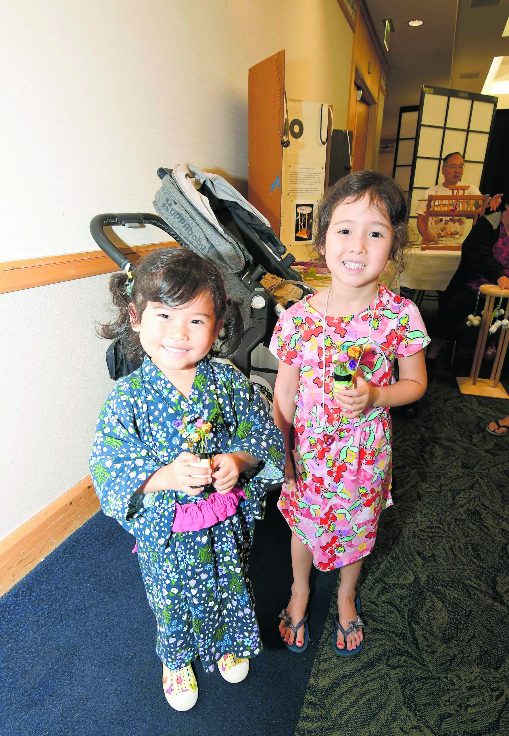 Lilia Yamamoto (left) and Ella Garst, both 4 years old, show off their make-and-take flower arrangement.