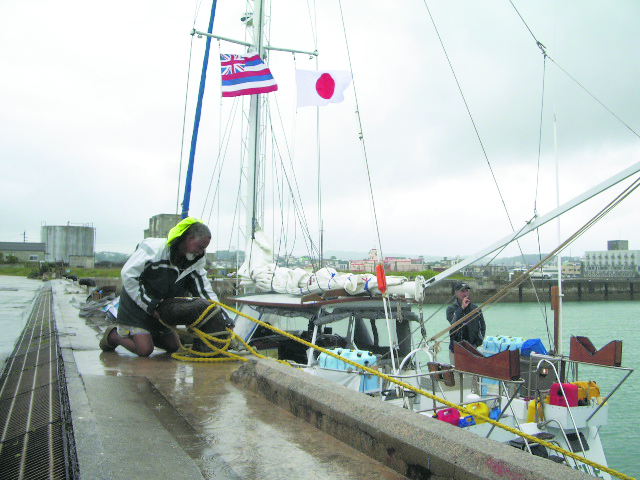 Under overcast skies, the flags of Hawai'i and Japan flutter in the wind as a crewmember secures some roping.