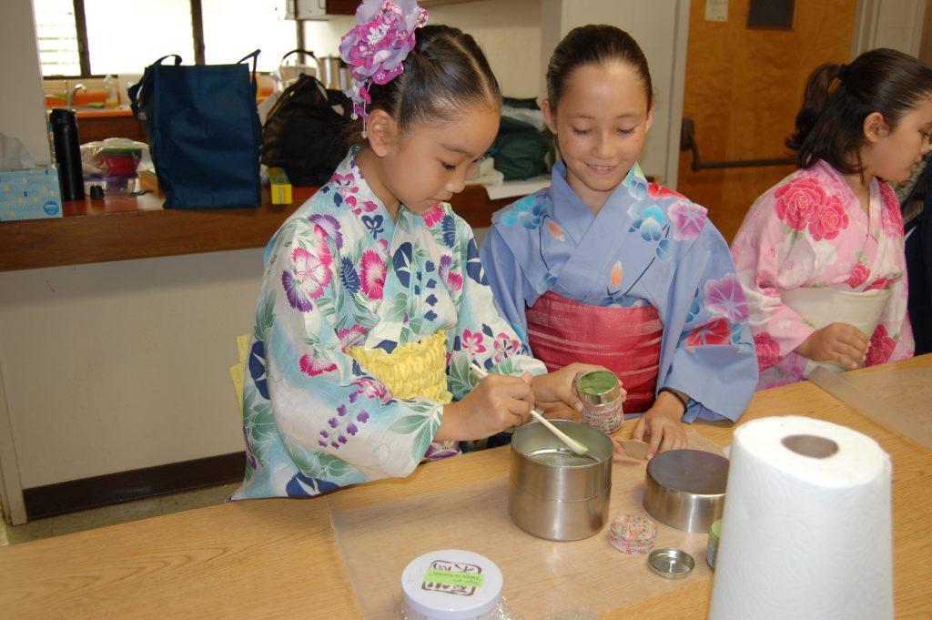 Aya Okimoto and Ai vanDeventer prepare the green tea powder they will use in tea ceremony class.
